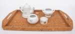 Cinco objetos utilitários: bandeja em cortiça (60 x 32cm) e 04 peças em porcelana branca: bule, cremeira, molheira e porta sache, total 05 peças.