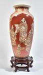 KYOTO SATZUMA - Excepcional Vaso japonês Séc. XIX período Meiji, em porcelana kyoto satzuma rouge fer, ricamente decorada c/ dignatária circundada por flores pintadas em policromia e realçada a ouro brunido, peanha em madeira, alt. 48cm, base 10cm, total 58cm.