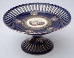 Fruteira estilo Luiz XV, em porcelana azul cobalto ao gosto de sevres decorada c/ cena galante policromada e dourada, med. 14 x 26cm.